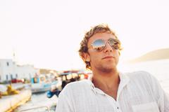 Handsome young man on vacation at sunset Stock Photos