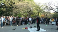 Street artist and crowd in beautiful Ueno park with autumn colors in Tokyo Stock Footage
