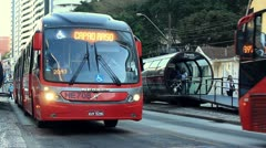 Two public buses stopping at bus stop in Curitiba, Brazil Stock Footage