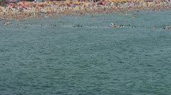 A lot of people at crowded bathing sandy beach.People swim in sea. Stock Footage