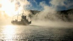 Ferry in sea smoke crossing fjord Stock Footage