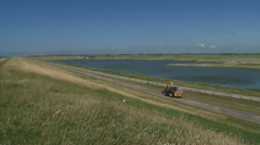 Tractor drives off in empty landscape + pan sea dike Stock Footage
