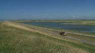 Stock Video Footage of tractor drives off in empty landscape + pan sea dike