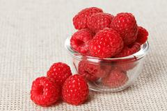 Still life with red raspberry and glass bowl on gray linen table cloth, copy  Stock Photos