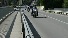 Bikers ride motorcycle people pass bridge road Stock Footage