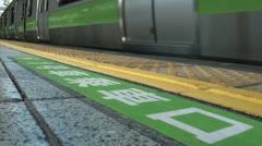 Low angle video of a commuter train departing the platform in Tokyo Japan Stock Footage