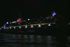 The Queen Mary 2 ocean liner slowly approaching at night - stock footage