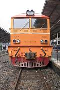 closeup of yellow diesel train locomotive on platform of bangkok railway stat - stock photo
