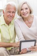 senior man & woman couple using tablet computer - stock photo