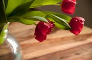Red tulips in a vase, which stands on the table Stock Photos