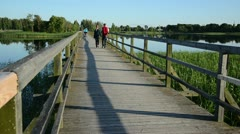 Young couple walk hand in hand on wooden bridge through lake Stock Footage