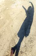Shadow of Woman on White Sand - stock photo