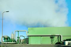 geothermal energy. a steam coming out from a small green power plant. - stock photo