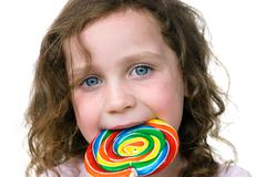 little girl smiling with her candy pin wheel sucker - stock photo