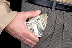 Man stuffing wads of cash into his pocket Stock Photos