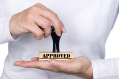 woman holding approval rubber stamp - stock photo