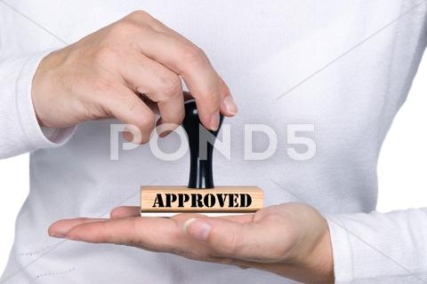 Stock photo of woman holding approval rubber stamp
