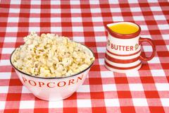 bowl of popcorn with cup of melted butter - stock photo
