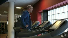 In a gym working out a bald and overweight man is running on a treadmill Stock Footage