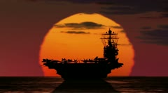 Silhouette of Aircraft Carrier against setting sun. Stock Footage