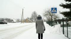 Woman walk street zebra crossing car go winter snow fall Stock Footage