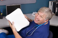 doctor holding a large manuscript - stock photo
