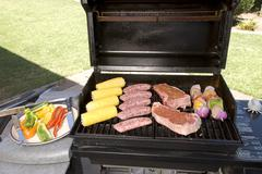 barbecue with steaks, brats chicken and corn - stock photo