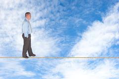 Businessman walking on tightrope Stock Photos