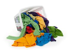 Bright clothes falling out of a laundry basket Stock Photos