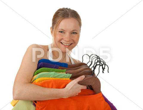 Stock photo of Charming young woman holding colourful clothes