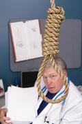 Doctor, noose and pile of paperwork Stock Photos