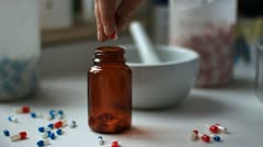 Pharmacist puts capsules in a jar Stock Footage