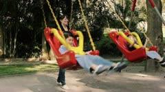 Mom Swinging Kids on Swings Stock Footage