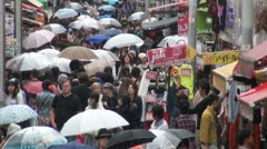Shoppers hold umbrellas during rain in the narrow Harajuku street in Tokyo Japan Stock Footage