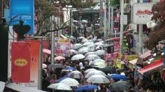 Harajuku shopping street in the rain, umbrellas in Tokyo, Japan - stock footage