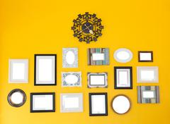 several frames with vintage clock on the yellow wall - stock photo