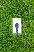 Energy concept outlet in  fresh spring green grass Stock Photos