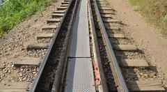 horizontal closeup of railway lines in sunlight - stock photo