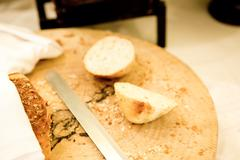 Wooden cutting board with sliced white bread and knife on wooden table Stock Photos