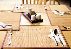 Table appointments- fork,knife,spoon, silk napkin on  bamboo mat Stock Photos