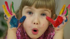 Close-up portrait of a girl. Girl hamming at camera. Baby covered in paint - stock footage