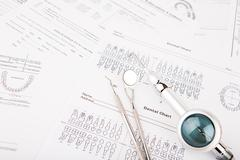 Dental tools and equipment on dental chart Stock Photos