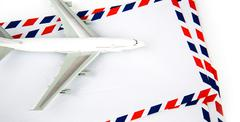 airmail envelope with model airplane - stock photo