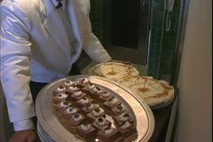 The Queen Mary 2, ocean liner, steward holding tray of desserts Stock Footage
