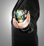 Business man holding the small world in his hands against white background (e Stock Photos