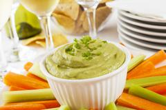 Guacamole with carrot and celery sticks Stock Photos