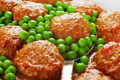 meatballs in sauce with peas - stock photo