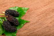 Mulberry and leaf on old wood Stock Photos