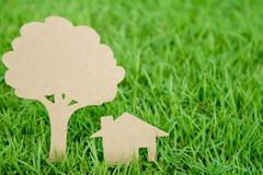 Paper cut of house and tree on fresh spring green grass Stock Photos