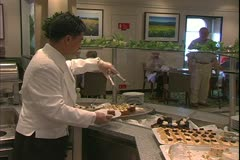 The Queen Mary 2, ocean liner, steward picks up desserts from buffet Stock Footage